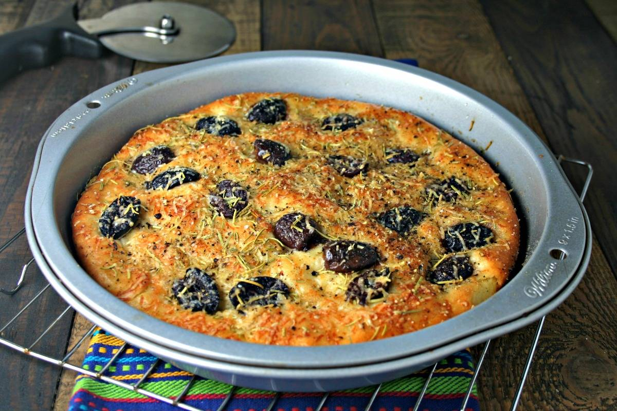 A pan of Greek olive focaccia bread sitting on a table