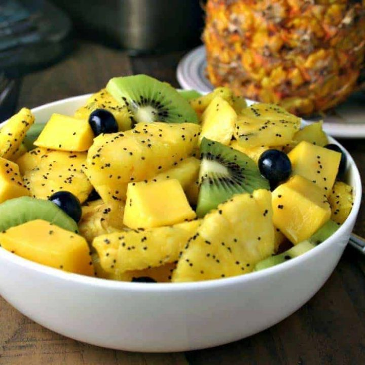 A bowl of fruit sitting on a table, with Tropical Fruit Salad with honey Lime Dressing