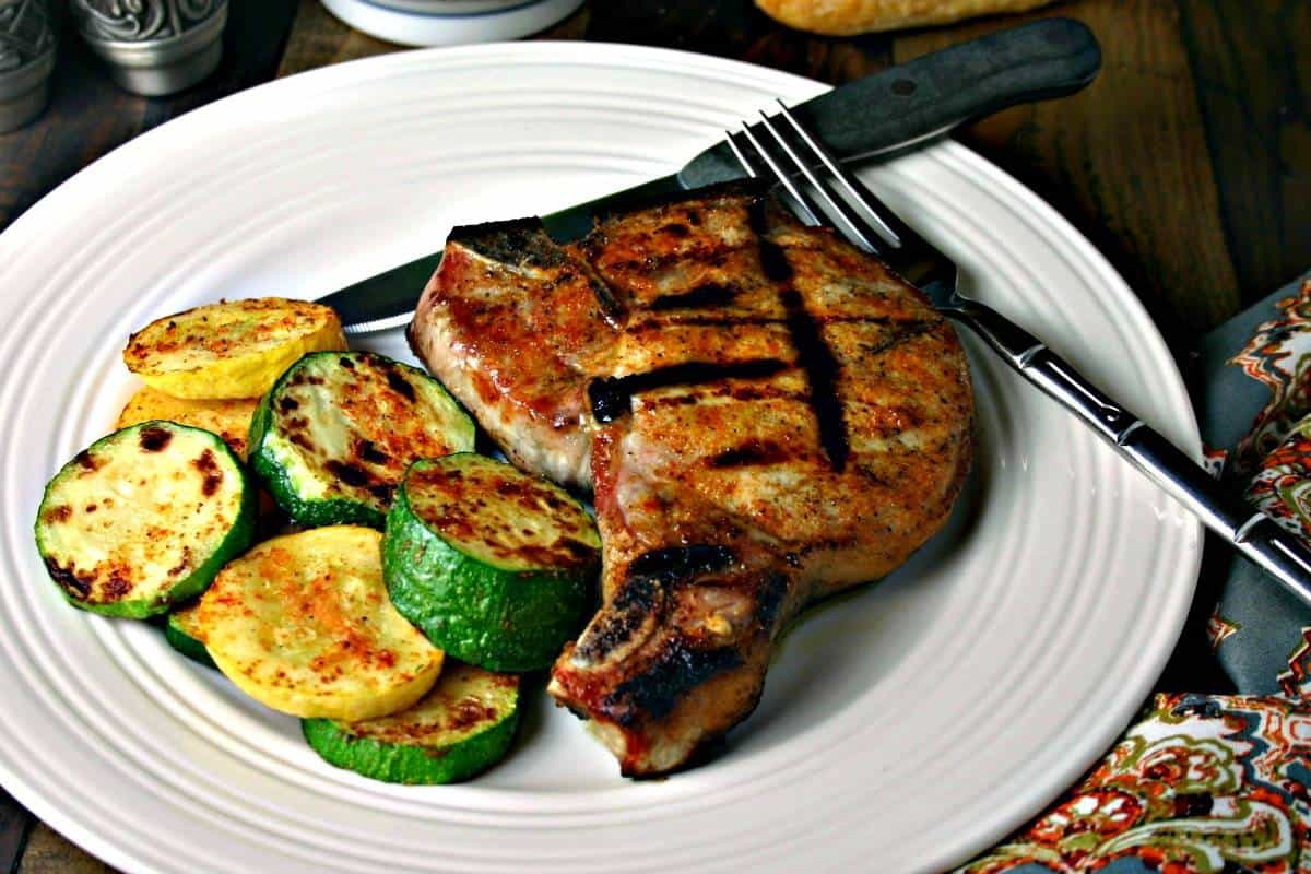 A plate of food on a table, with pork chop and zucchini
