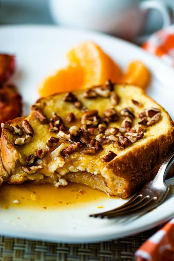 french toast with pecans and oranges on a white plate