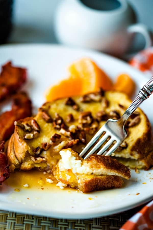 A plate of food with a fork, with French toast