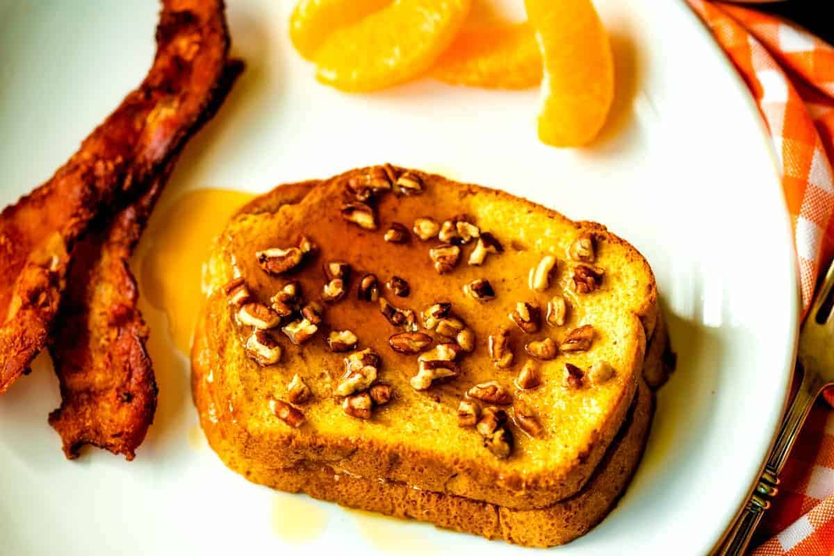 A piece of French Toast on a plate, with pecans and maple syrup