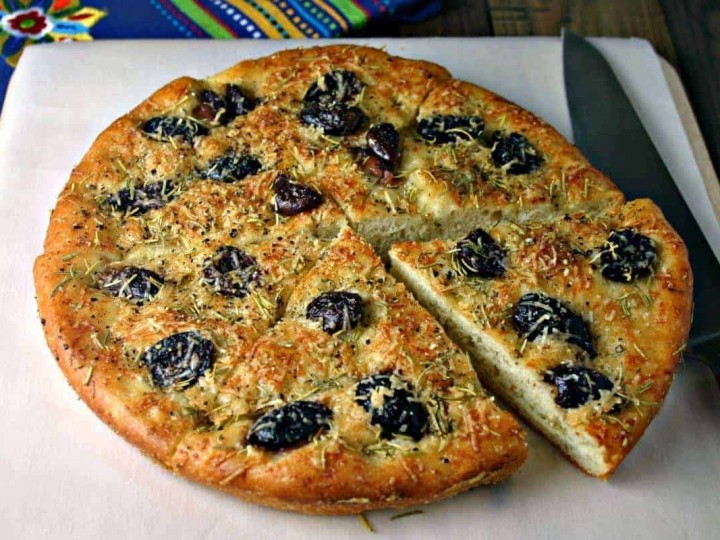 Greek olive focaccia bread sitting on top of a wooden cutting board