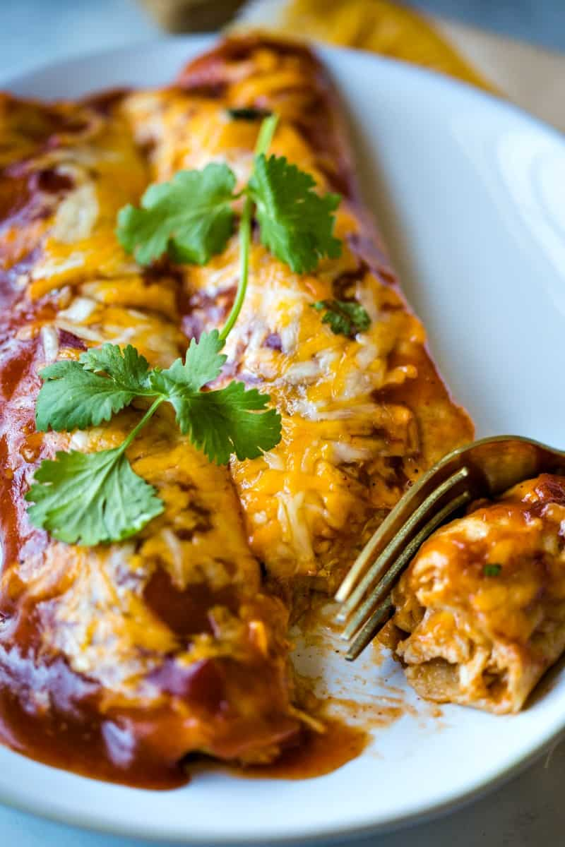 a fork cutting into chicken enchiladas on a plate