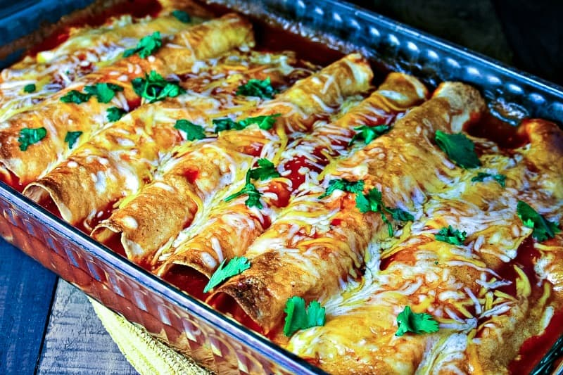 A baking dish sitting on top of a table, with Chicken and Cheese Enchiladas