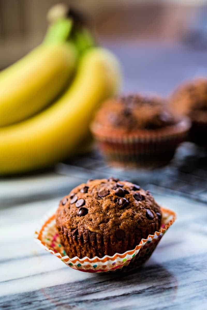 a chocolate banana muffin on a marble counter with the paper lining peeled off