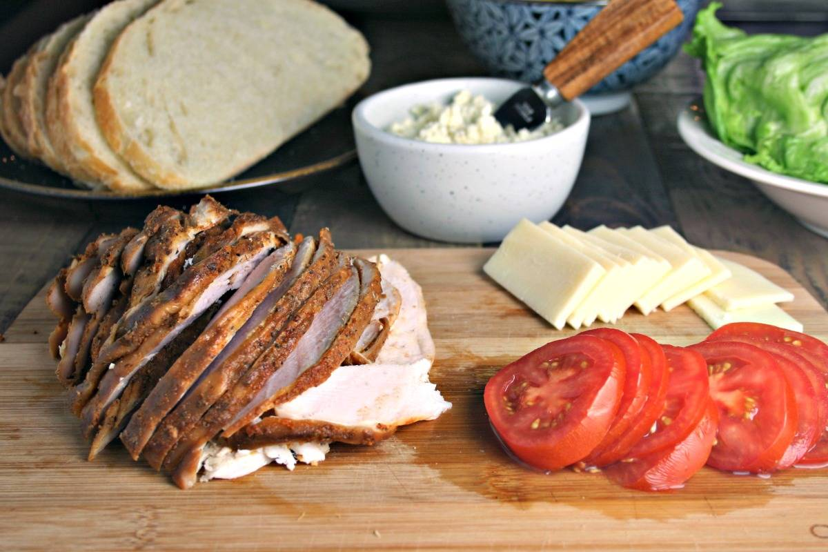 Sliced turkey, tomatoes, and cheese on a wooden cutting board, with Turkey Stack with Feta Spread