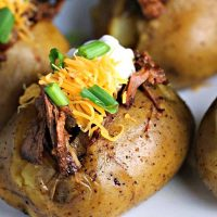 A close up of Slow Cooker Beefy BBQ Spuds, potatoes
