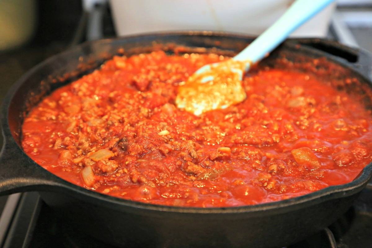 A close up of an iron skillet filled with Homemade Red Chili