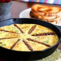 An iron skillet of Rustic Sausage and Grits Egg Skillet