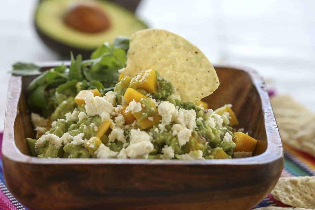 A close up of a bowl of mango guacamole