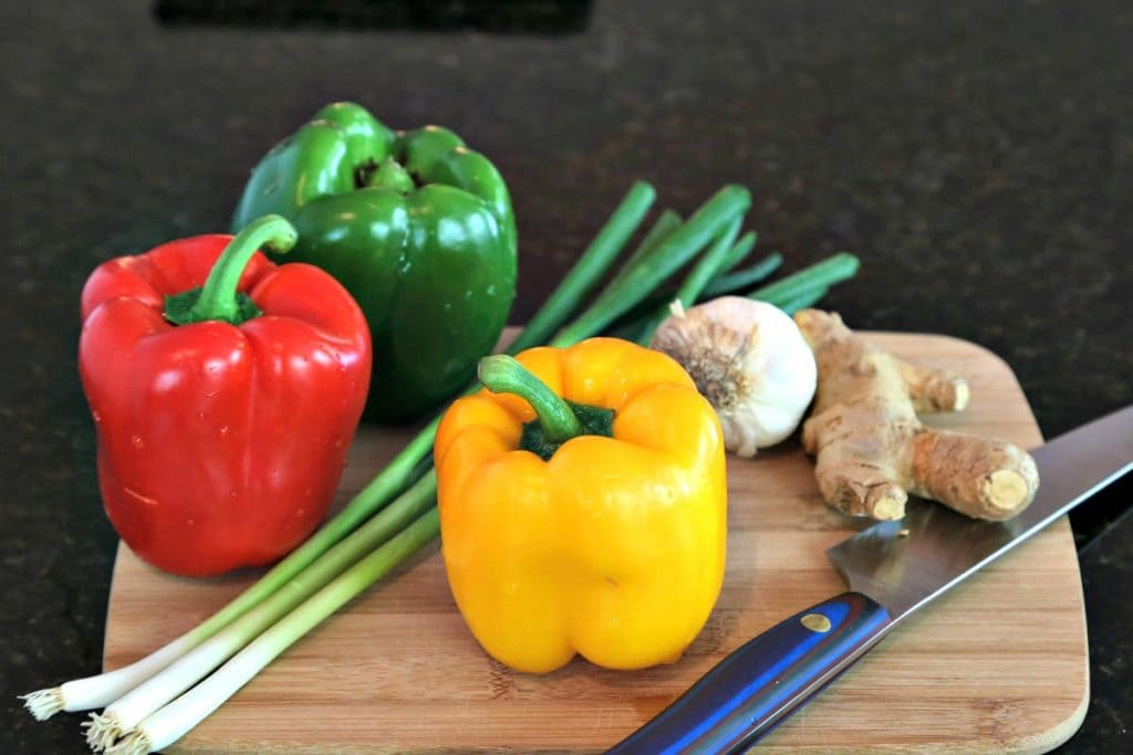 A close up of ingredients for Pepper Steak Stir-Fry with bell peppers, garlic, and ginger
