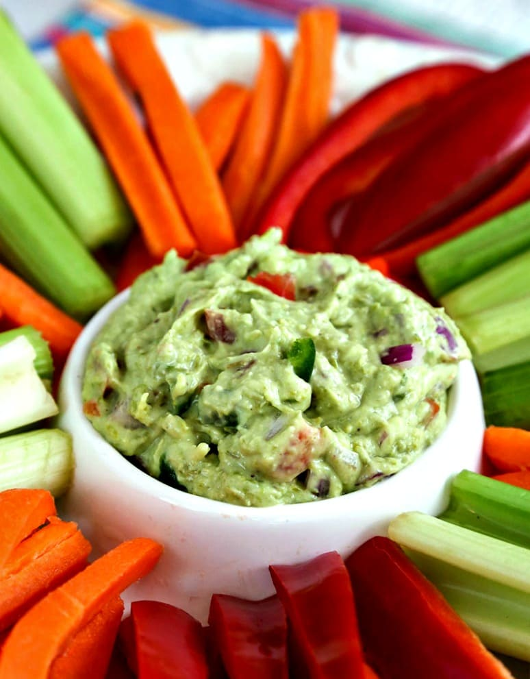 A platter with carrots, celery, and bell peppers, with Secret Ingredient Guacamole