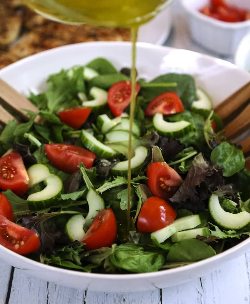 A bowl is filled with salad ingredients, with Sesame Chicken Salad