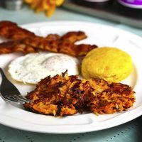 A plate of food with a fork, with fried egg, biscuit, and Sweet Potato Hash Browns