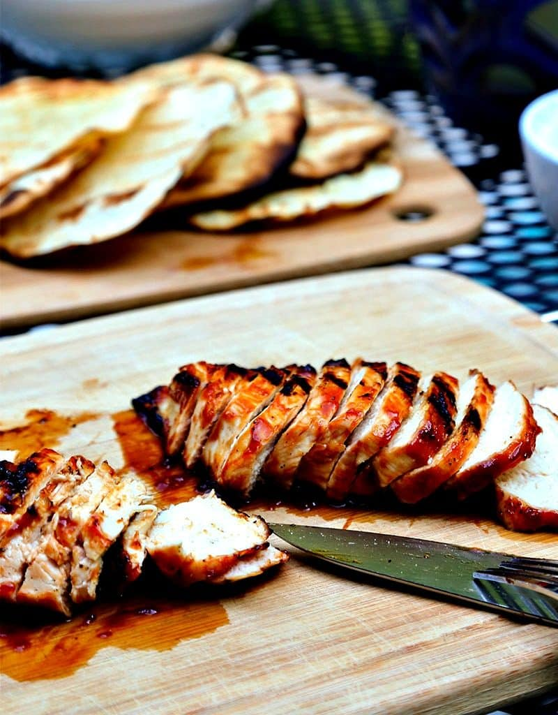 Slices of chicken sitting on top of a wooden cutting board, with BBQ Chicken Tostadas