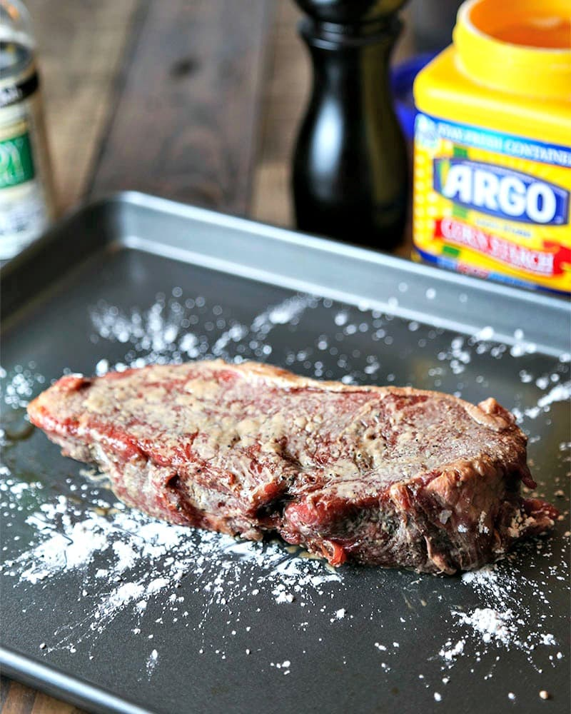A close up of a steak dusted with cornstarch
