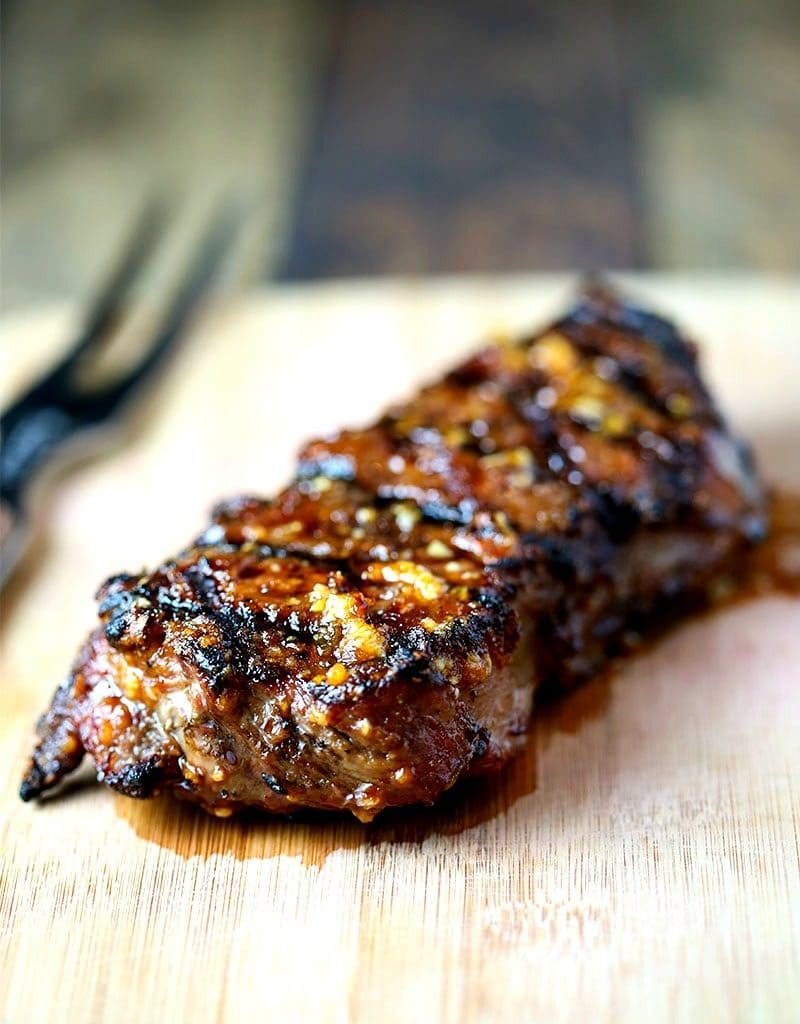 A Mongolian Glazed Grilled Steak on top of a wooden cutting board
