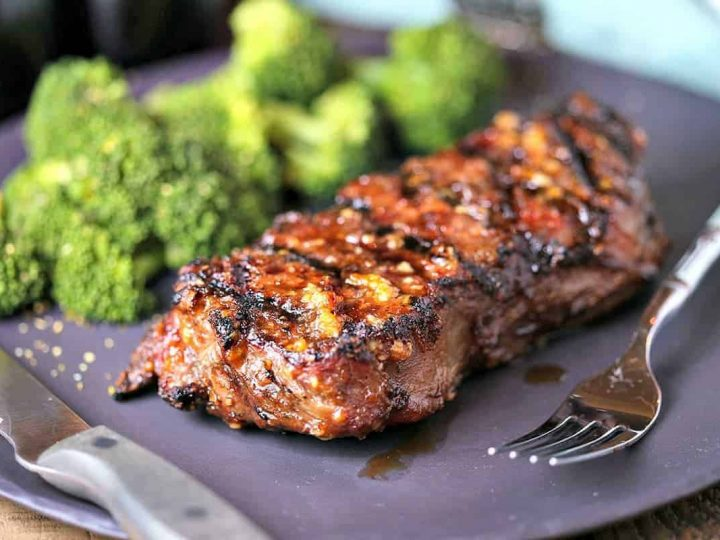 A close up of a plate of Mongolian Glazed Grilled Steak with a fork and knife