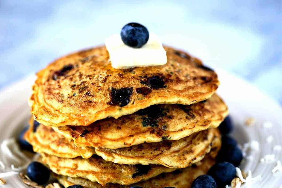 A close up of a stack of blueberry coconut oatmeal pancakes on a plate