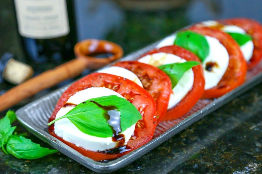 A tray of caprese salad with fresh basil