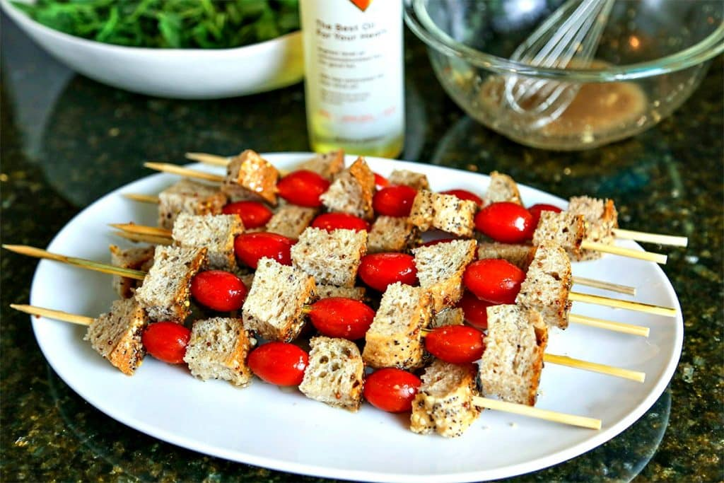 A plate of bread and tomato skewers