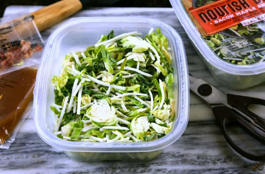 A plastic container of shredded brussels sprouts
