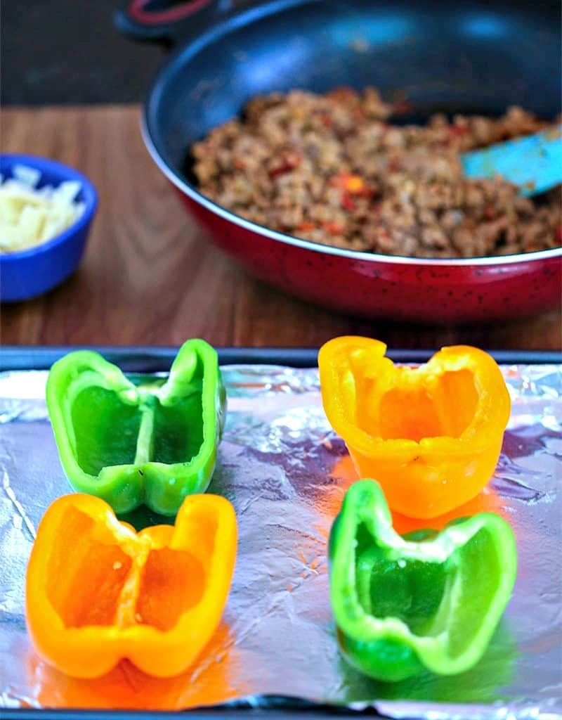 Green and yellow bell peppers halves on a baking sheet