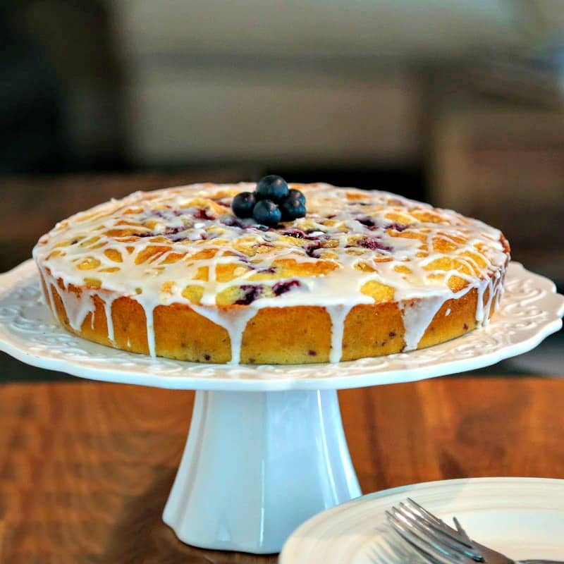 Blueberry Coffee Cake on a cake stand on top of a table