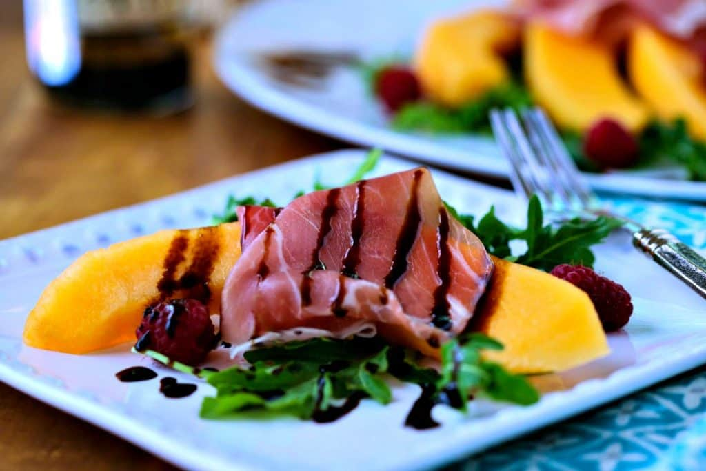 A plate of Cantaloupe and Prosciutto drizzled with balsamic vinegar
