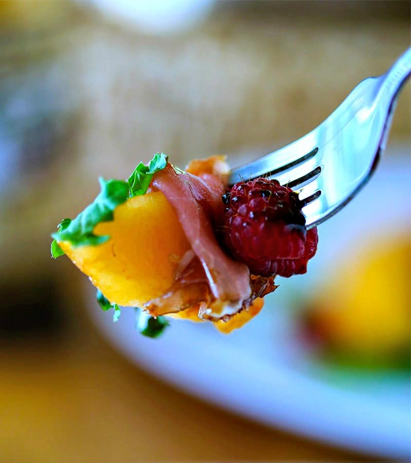 A close up of a piece of Cantaloupe, Prosciutto, and raspberry