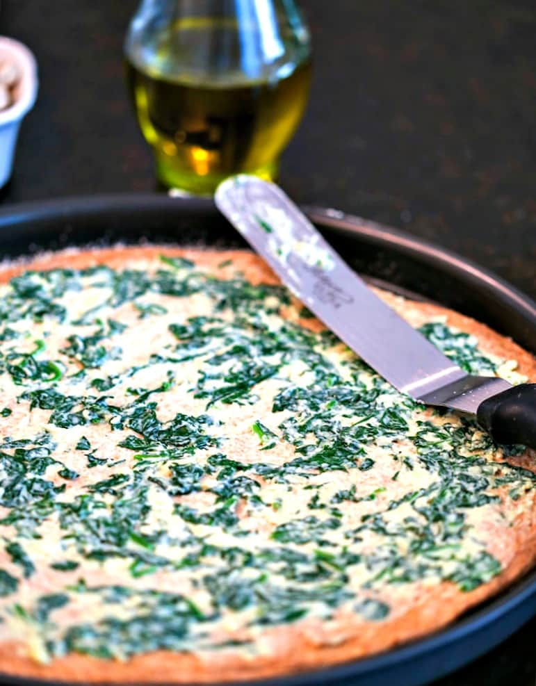 A pizza crust spread with spinach mixture