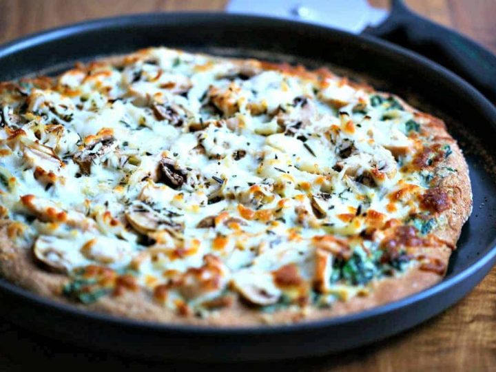 A chicken florentine pizza sitting on top of a pan on a table