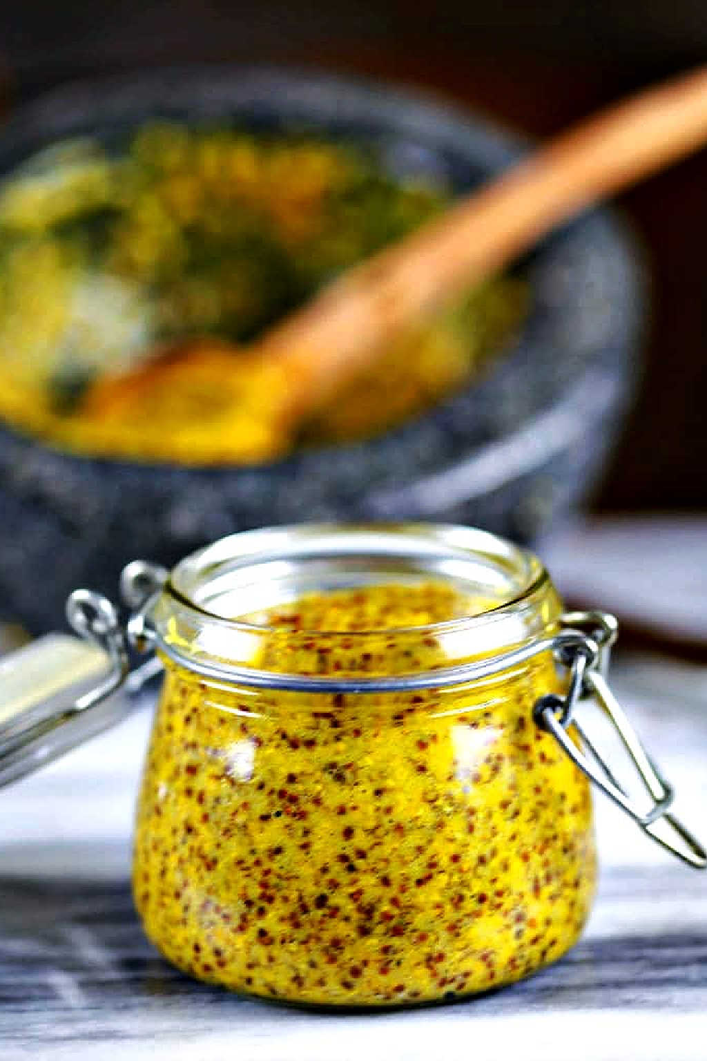 homemade stone-ground mustard in a glass jar on a counter.