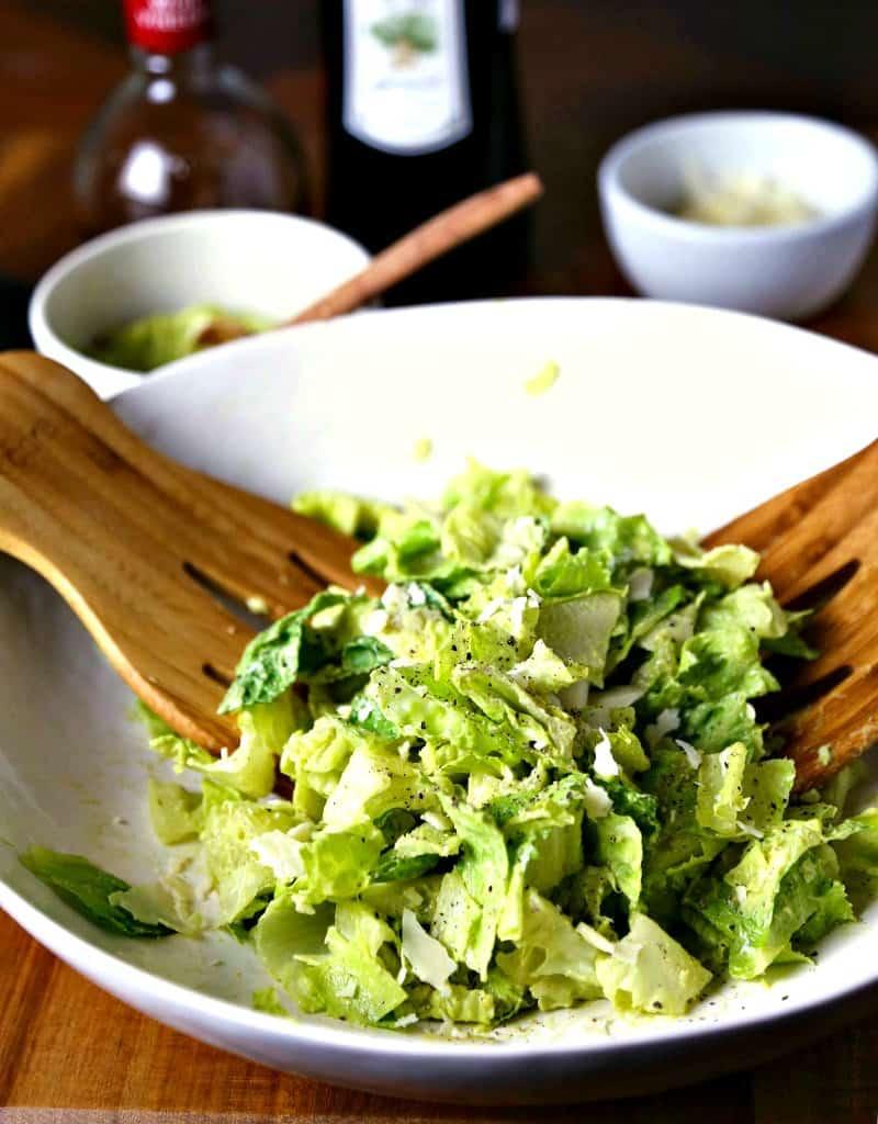 A bowl of salad, with avocado caesar dressing