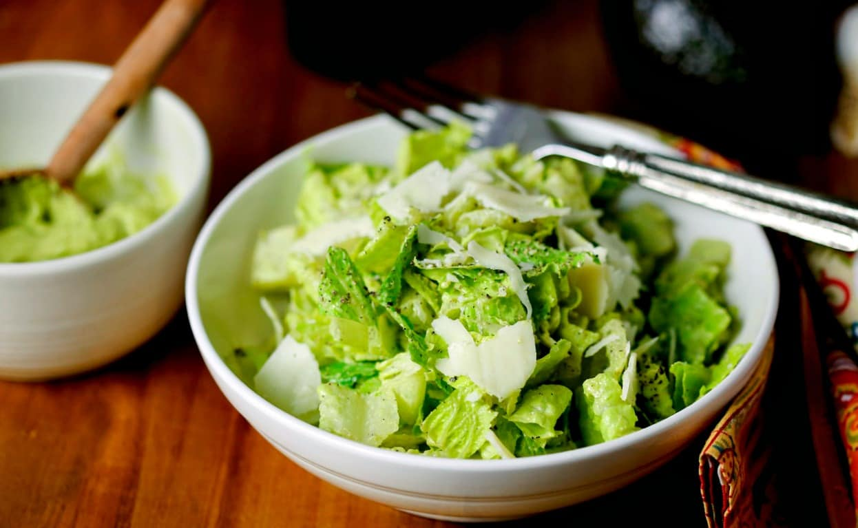 A close up of a bowl of salad, tossed with avocado caesar dressing