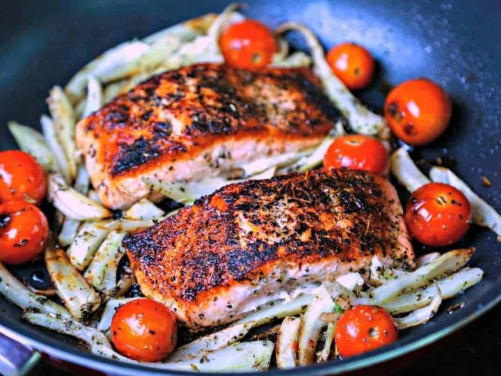 A skillet of Mediterranean Salmon on top of fennel and tomatoes