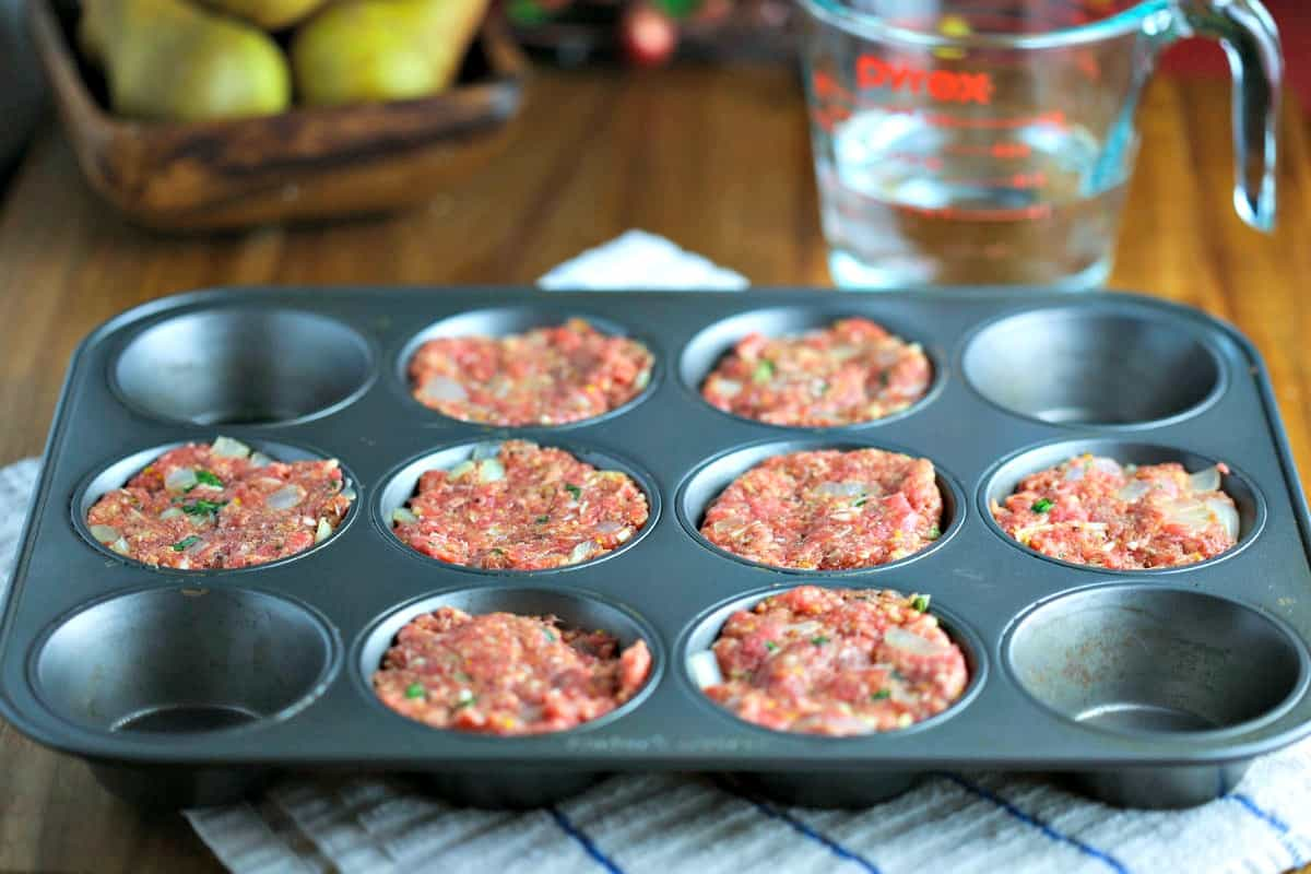 A muffin tin with meatloaf mixture on a table