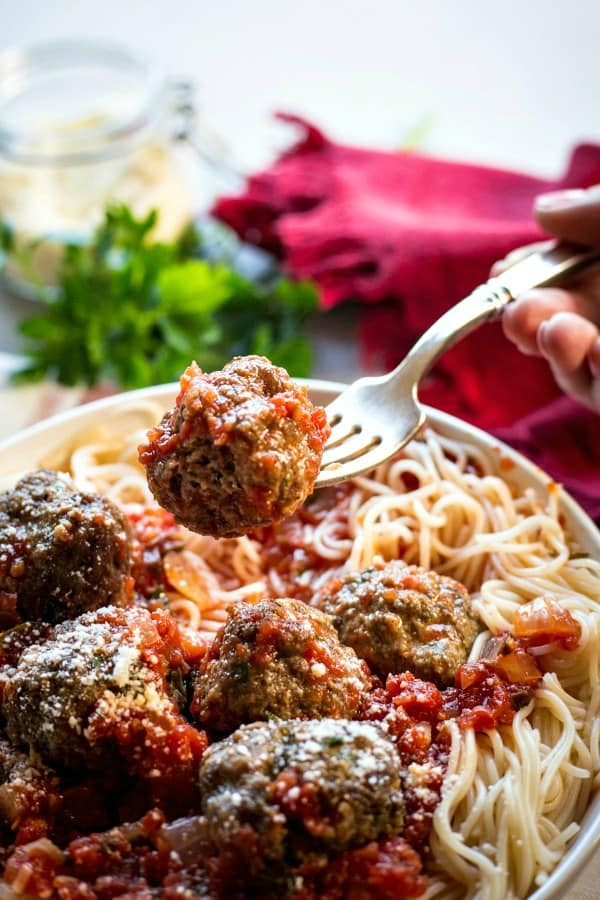 A close up of a plate of food, with Meatball and Spaghetti