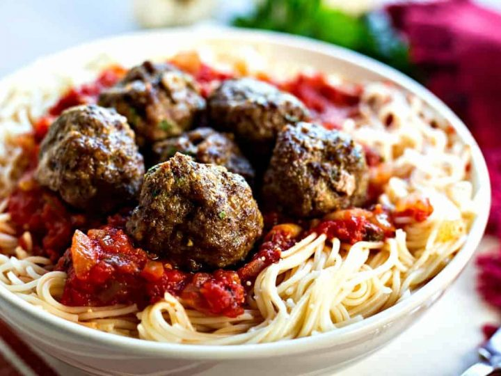 A dish is filled with food, with spaghetti and meatballs