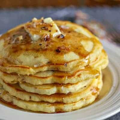 Coconut Pecan Pancakes with butter and maple syrup on white plate