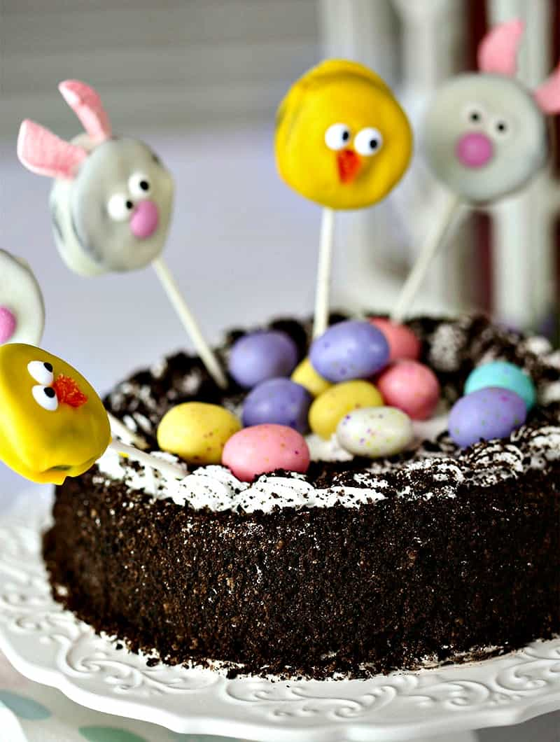 """Hop on into Spring with this adorable Easter dessert, an Oreo Ice Cream Cake decorated with a """"nest"""" of speckled Easter eggs and crowned with pink bunny and yellow chick Oreo cookie pops!IceCreamCakeBreak #sponsored"""