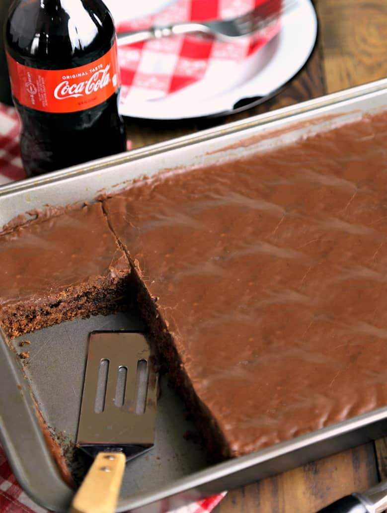 A bottle of Coca Cola on a table with chocolate cake