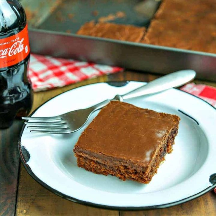 A piece of cake on a plate on a table, with Chocolate Coca-Cola Cake