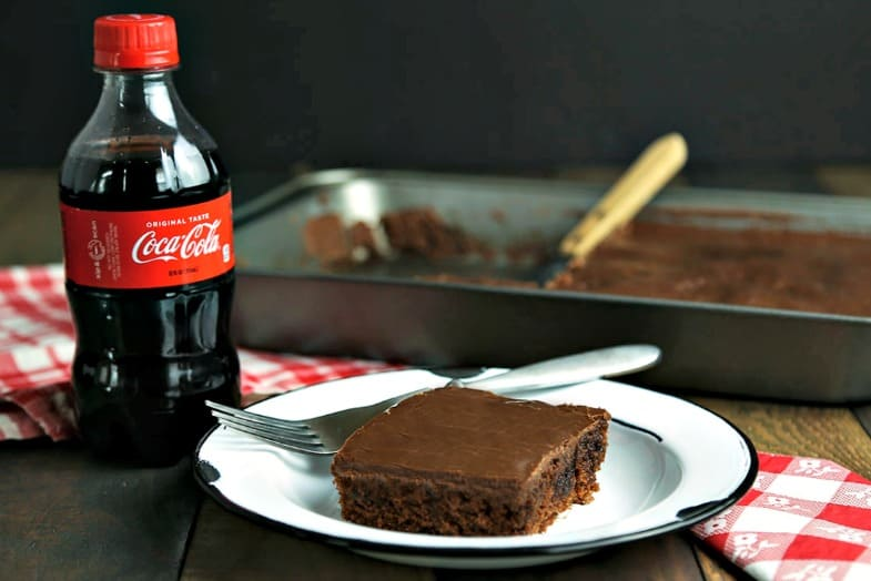 A bottle of Coca Cola with a slice of cake on a plate, with Classic Coca-Cola Chocolate Cake