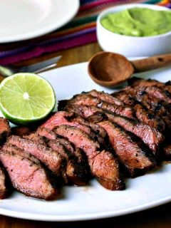 A plate of food on a table, with sliced grilled steak for fajitas