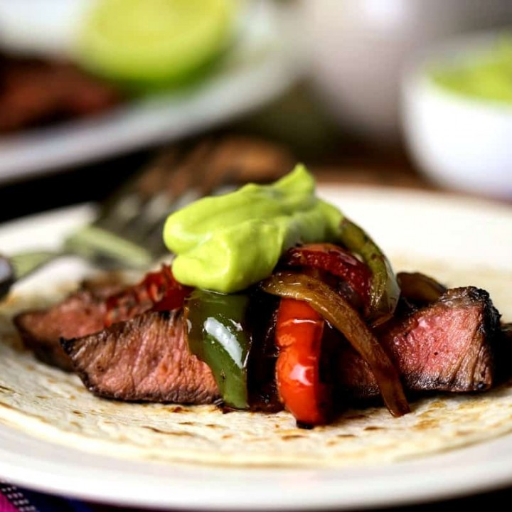 A plate of food on a table, with grilled steak fajitas and guacamole