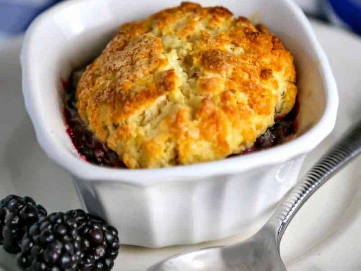 Mini Blackberry Cobbler in a ramekin on a plate with blackberries