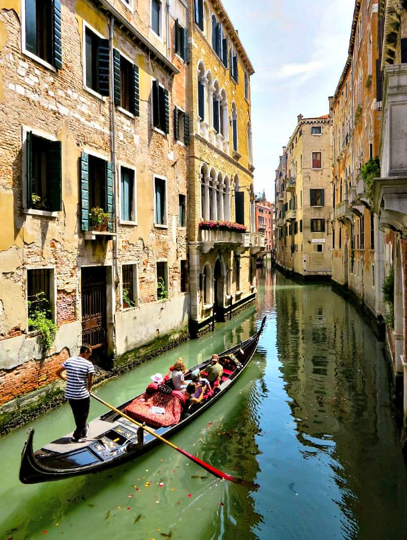 A gondola on a canal with Venice in the background