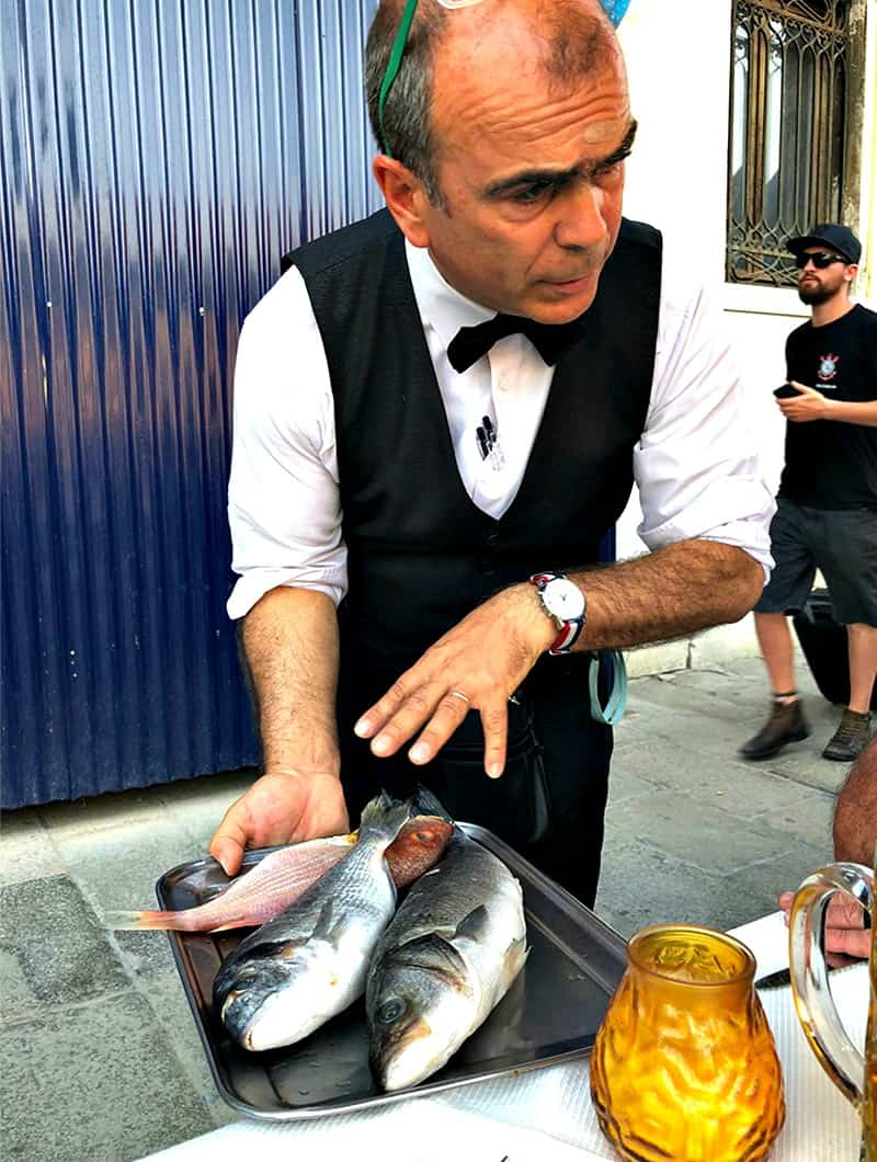 A man holding a tray of fish